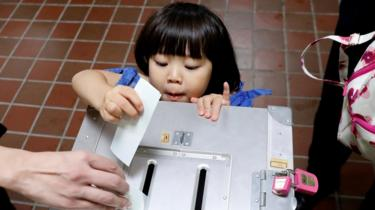 A girl casts her father's ballot for a national election at a polling station in Tokyo, Japan October 22, 2017