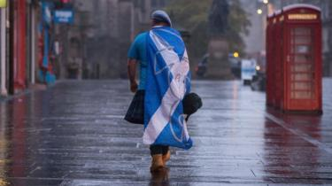 "A lone ""YES"" campaign supporter walks down a street in Edinburgh"
