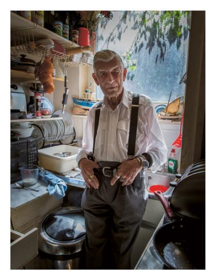مسن يقف في مطبخ.