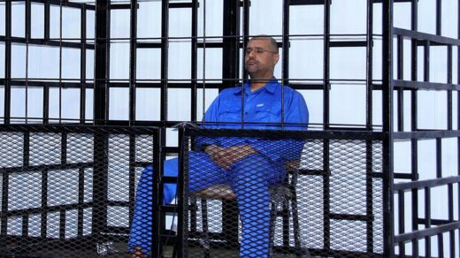 Saif al-Islam Gaddafi, son of late Libyan leader Muammar Gaddafi, attends a hearing behind bars in a courtroom in Zintan, 25 May 2014