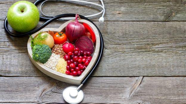 Grupo variado de alimentos con un estetoscopio en forma de corazón.