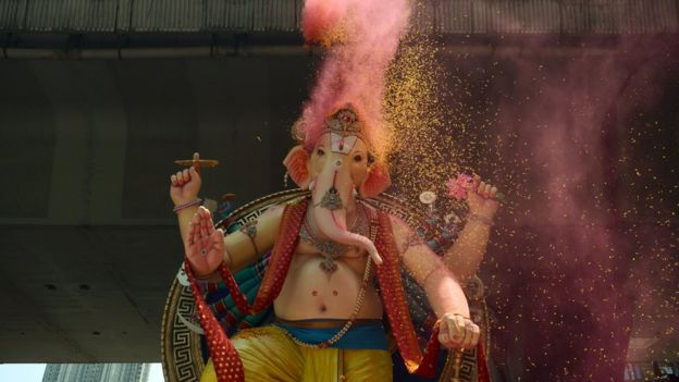 An Indian devotees shower rose petals and coloured powder on a huge idol of elephant-headed Hindu deity Ganesha during its procession for an immersion in Mumbai on September 5, 2017.