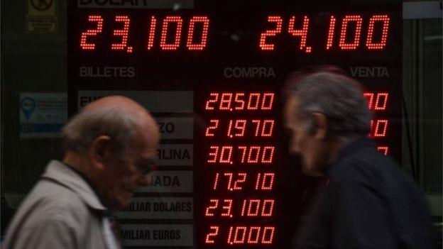 Dos hombres pasando frente a una casa de cambio en Buenos Aires.