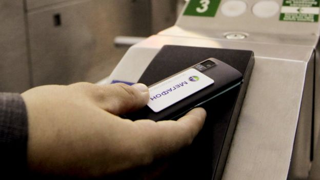 Mobile payment. A cell phone being used to pay for a metro train ticket. The handset is fitted with a smart card that allows near-field communication (NFC), a contactless technology that enables the handset to communicate with the ticket barrier