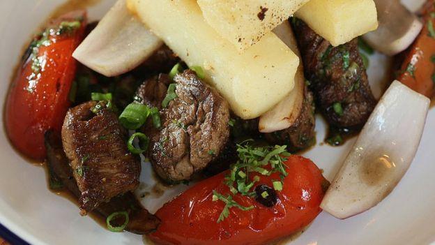 Plato peruano lomo saltado. Contiene carne, cebolla, tomate y papas.