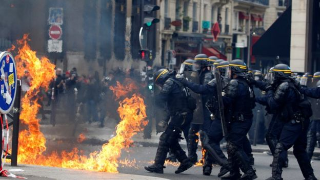 French riot police protect themselves from flames during clashes at traditional May Day labour union march in Paris, May 1, 2017