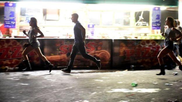 Pessoas correndo da cena do tiroteio