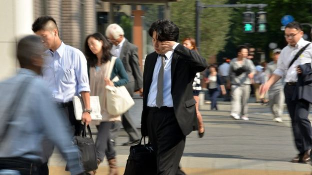 A Japanese businessman walks with sleep in Tokyo.