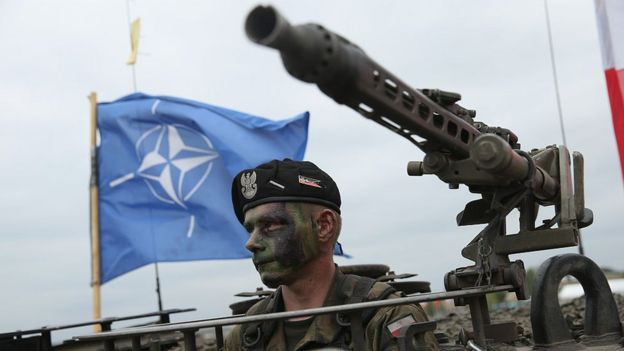 Soldado con la bandera de la OTAN atrás.