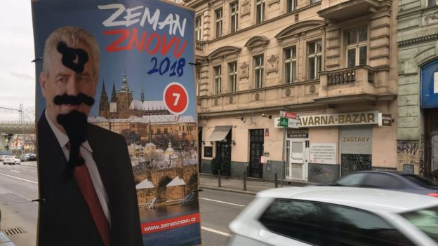A defaced Zeman poster tied to a lamppost in Prague