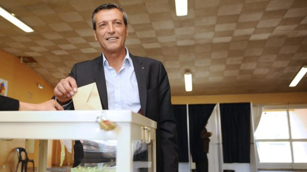 Edouard Martin votes in a centre while smiling at the camera in his election