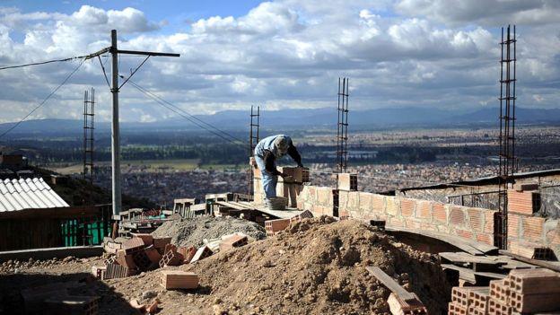 Un albañil construyendo una casa en un cerro de Bogotá.