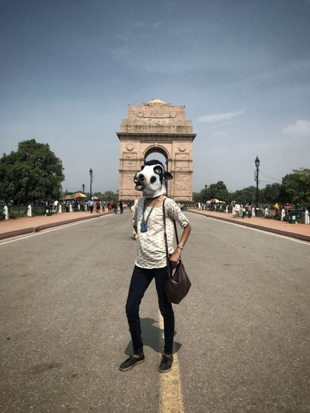 A woman with a cow mask in front of Delhi's India Gate