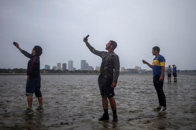 The Tampa skyline is seen in the background as local residents (L-R) Rony Ordonez, Jean Dejesus and Henry Gallego take photographs after walking into Hillsborough Bay ahead of Hurricane Irma in Tampa, Florida, 10 September