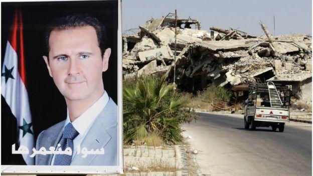 Un poster con el rostro de Bashar al Asad junto a un edificio destruido