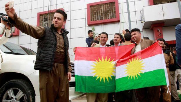 أكراد يلتقطون صورا مع علم إقليم كردستان العراق