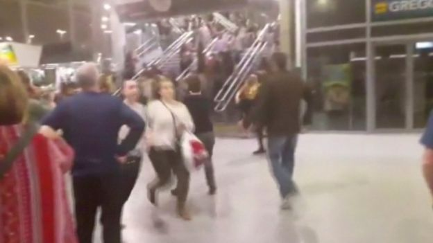 People running down stairs as they attempt to exit the Manchester Arena