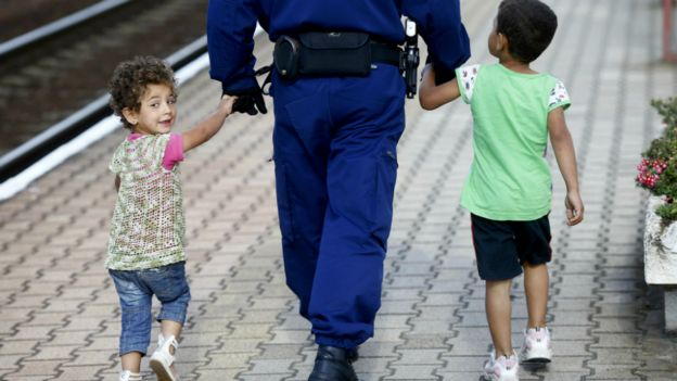 A police officer escorts migrant children along a platform at a railway station in Hegyeshalom, Hungary - 7 September 2015