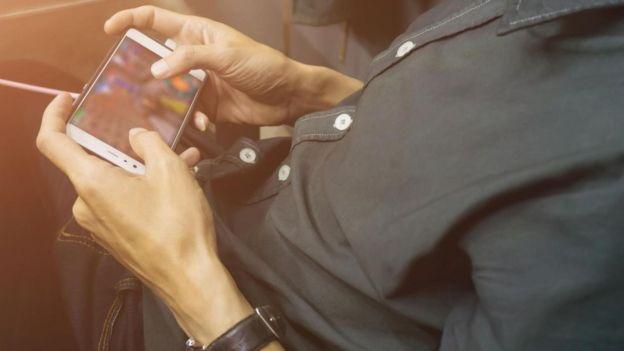 Un hombre jugando con su teléfono celular