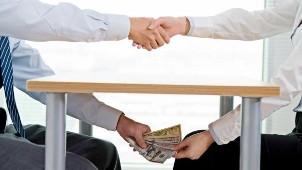 Pessoas passam dinheiro por debaixo da mesa