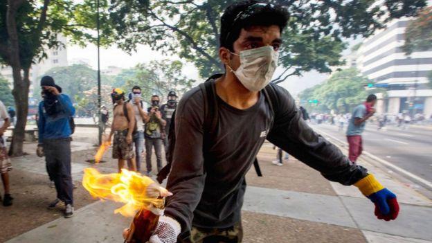 Una manifestante de oposición lanza un cóctel molotov a la policía.