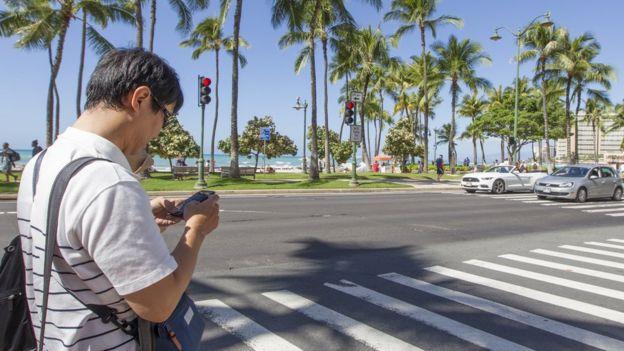 hombre usando celular en las calles de Hawái.