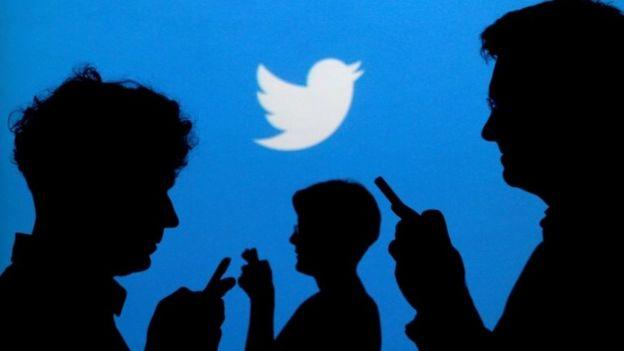 Personas que usan sus teléfonos delante de un logotipo de Twitter