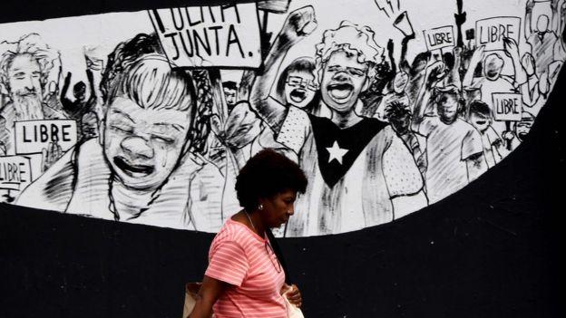 Un mural en Puerto Rico con personas sosteniendo carteles que dicen:
