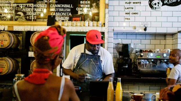 A woman buys a drink from the hipster coffee store 'House of Machines' on March 31, 2017 in Cape Town, South Africa.