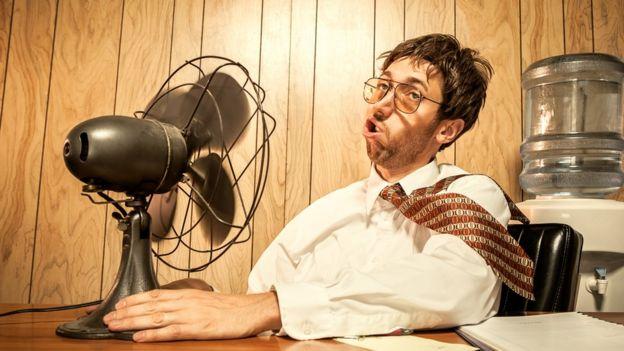 Hombre en la oficina frente a ventilador.
