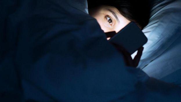 Una persona mirando su teléfono, en cama y en la oscuridad