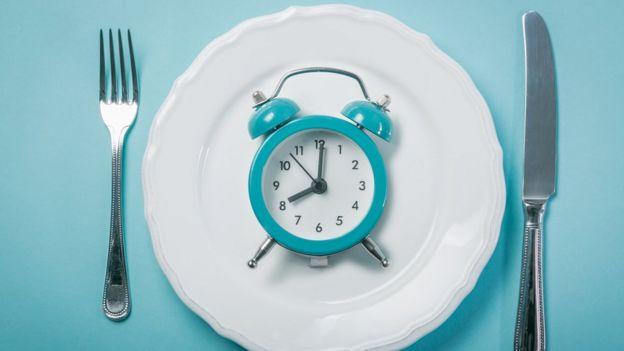 Imagem mostra um despertador dentro de um prato com talheres ao redor