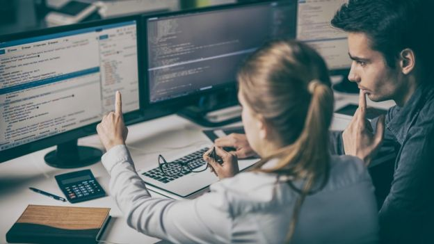 Mujer y hombre miran pantallas de computadora.