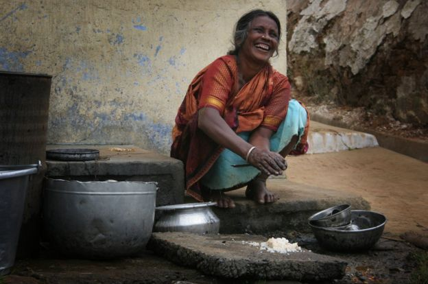 A woman washing dishes in India.