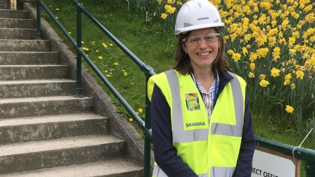 Skanksa employee Kate Young standing by some railings wearing a hard hat and high-vis jacket