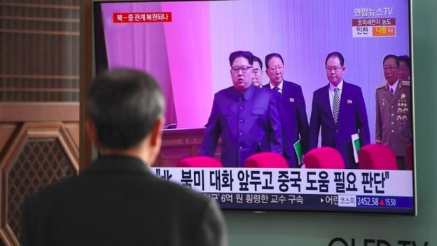 Man watches Japanese news report about possible visit by North Korean leader