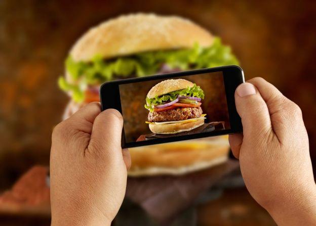 Hombre tomándole una foto con su celular a una hamburguesa.