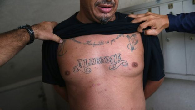 U.S. Immigration and Customs Enforcement (ICE), agents inspect an immigrant's tatoos while detaining him on October 14, 2015 in Los Angeles, California.