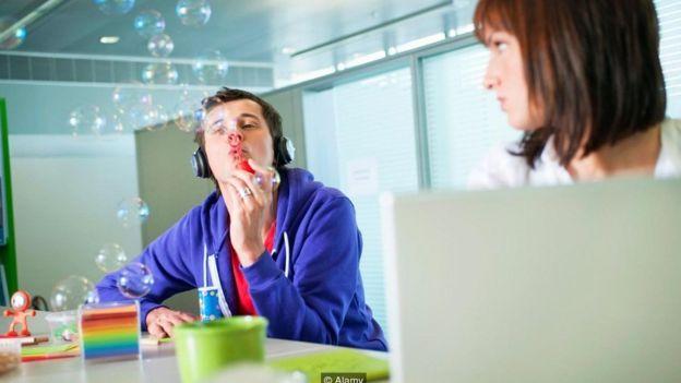 Un empleado hace burbujas de jabón en la oficina