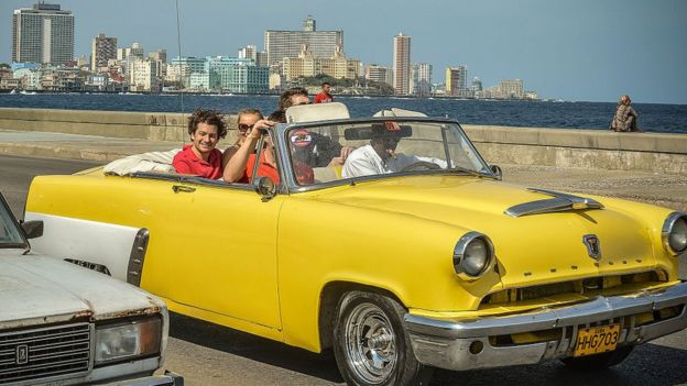 Turistas paseando en un auto antiguo en La Habana.