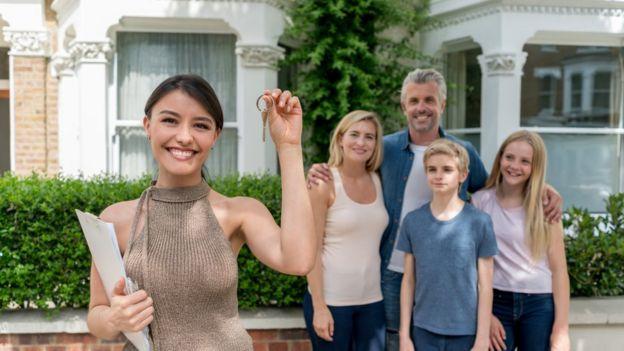Una chica enseña la llave de su nueva casa