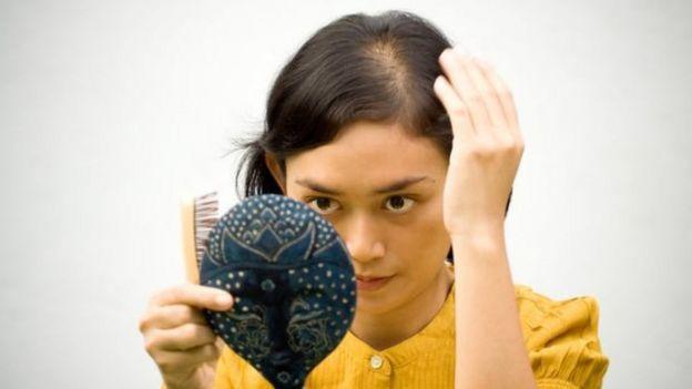 Mulher observa superfície de sua cabeça
