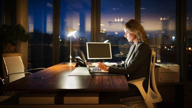 Una mujer trabajando de noche en una oficina solitaria