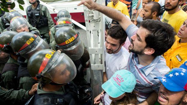 Manifestantes frente a la policía.