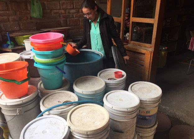 Vecina de Iztapalapa enseña agua recolectada.
