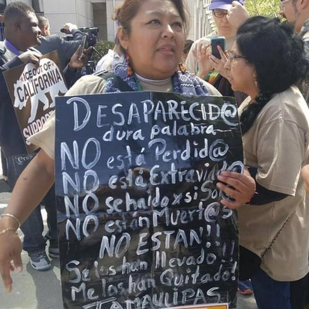 Graciela Pérez Rodríguez con una pancarta que dice