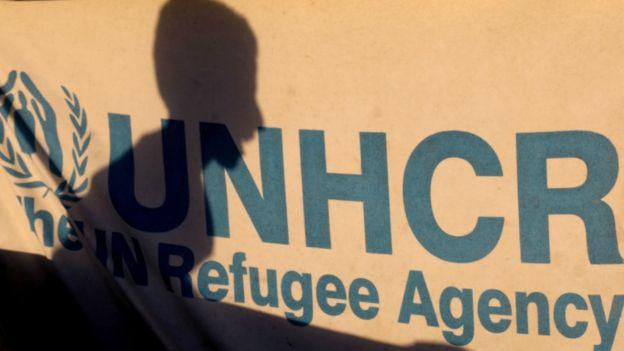 La sombra de un menor desplazado en Siria sobre un letrero de ACNUR en un campo de refugiados de Ain Issa, julio 11 de 2017