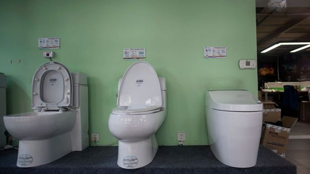 Models of the 'Auto-cover Changing toilets' are on display in a showroom of Trump Toilet products in Shanghai on November 18, 2016