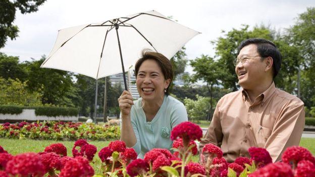 Una mujer asiática cubriéndose del sol junto a un hombre