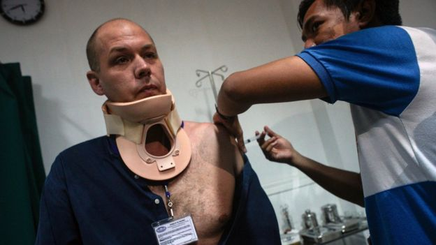 Adam Harvey in a neckbrace, being attended to by medical staff in a hospital